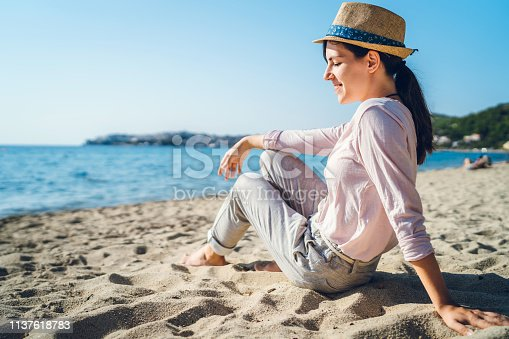 Young beautiful woman is sitting on the beach and enjoying the view