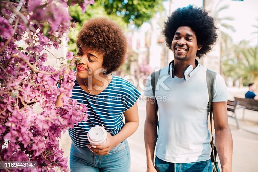 Young African - American couple smelling the flowers and enjoying their honeymoon together.