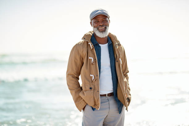 Enjoying the comfortable retirement I worked hard for Portrait of a mature man enjoying a day at the beach hands in pockets stock pictures, royalty-free photos & images