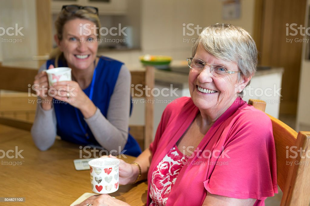 Enjoying the Company! Community care worker joins an an elderly woman for a cup of tea while sitting at her kitchen table. 30-39 Years Stock Photo
