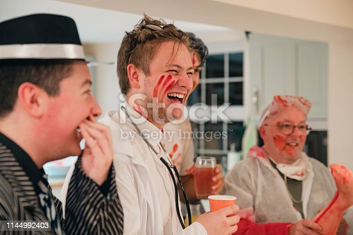 Group of work friends dressed up and laughing at a Halloween party. They are all men and some are holding drinks.