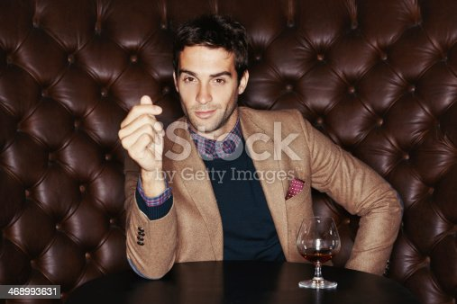 Portrait of a handsome young man drinking in a club