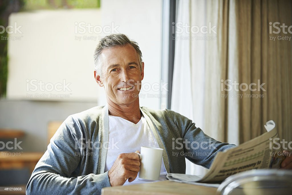 Enjoying the first cup of coffee and morning paper stock photo