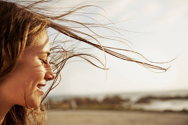 Enjoying the fresh sea air Cropped view of a young woman with the wind in her hair positive emotion stock pictures, royalty-free photos & images