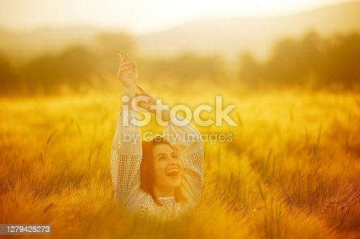 Redhead enjoying the golden hour in the agricultural field looking up laughing raising arms