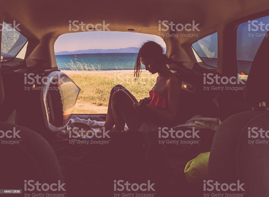 Enjoying the life... Photo of young stylish woman enjoying the view at the seashore from the car trunk 20-29 Years Stock Photo