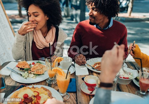 Afro-american couple enjoying healthy lunch with friends in restaurant outdoor