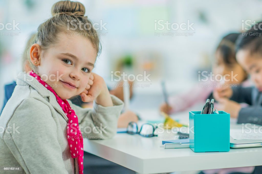 Young girl sits at an office desk looking at the camera with a smile...