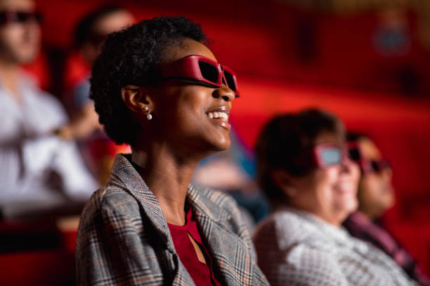 Enjoying the Movie Young female adult sitting in a movie theatre, wearing 3D glasses. She is enjoying and laughing at the movie. 3 d glasses stock pictures, royalty-free photos & images