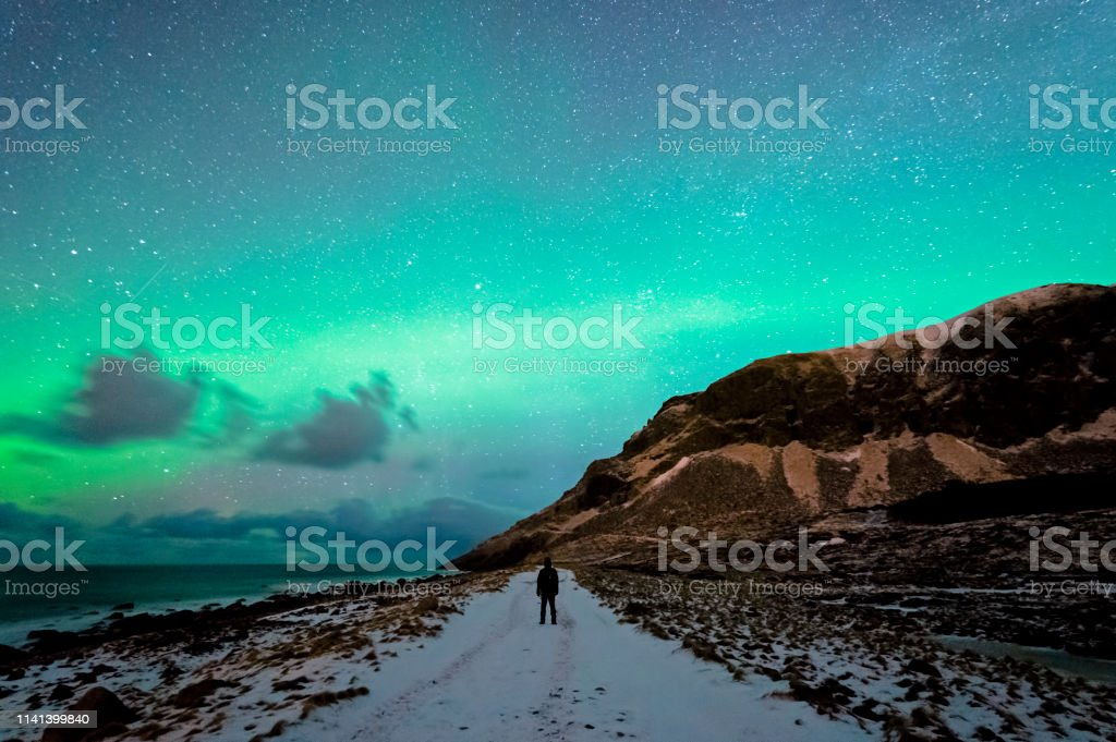 Enjoying the Northern Lights in Unstad Enjoying the sky with Northern lights spotted in Unstad, Lofted in a cloudy sky. Adventure Stock Photo