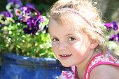 Young girl enjoying the garden outside, in the sunshine.