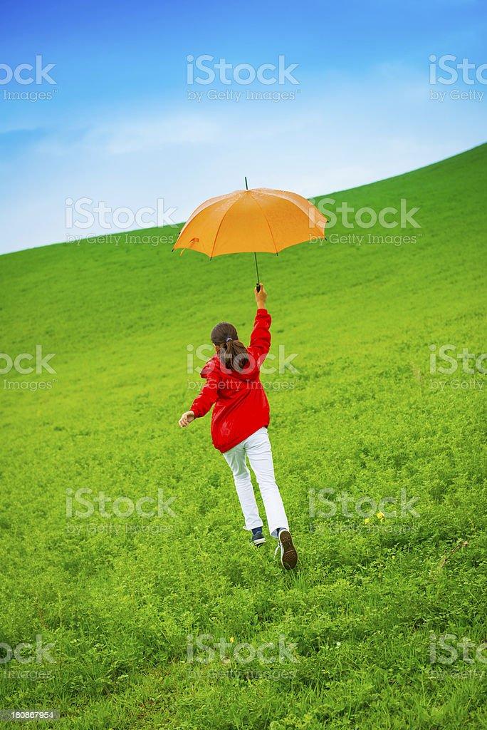 Young girl enjoying the rain in green Tuscany fields.