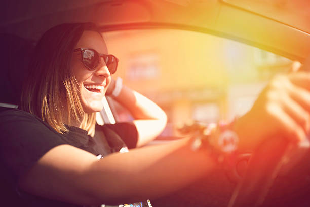 Enjoying The Ride Smiling young woman driving a car. one young woman only stock pictures, royalty-free photos & images