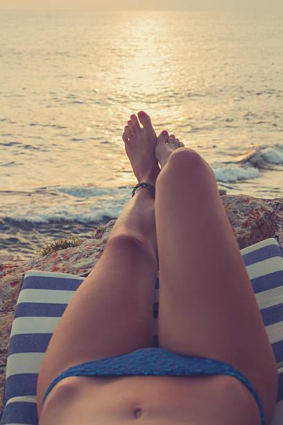 enjoying the sea / ocean. - woman leg beach pov stock photos and pictures