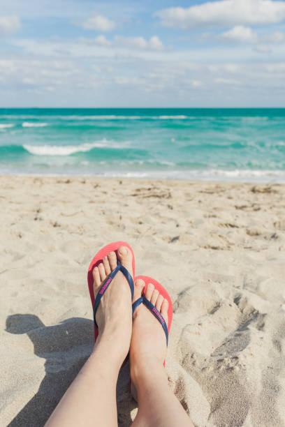enjoying the sea - woman leg beach pov stock photos and pictures