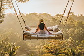 Photo of a young woman sitting on the swing.  Jungle Bed hanging over the tropical forest with Caucasian female resting while looking at the view, Bali, Indonesia. Rear view of a female sitting and enjoying the view.