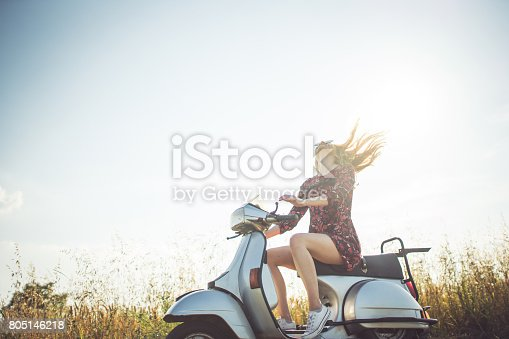 Young woman sitting on the motorcycle on the countryside