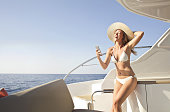 Beautiful woman in white bikini with a big hat standing on a yacht laughing while reading something on her smartphone
