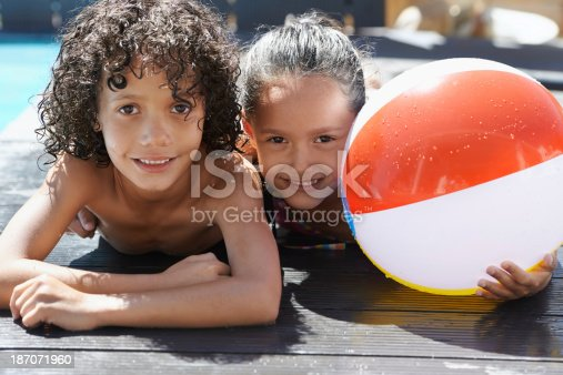Portrait of two children lying by a swimming pool on a sunny day