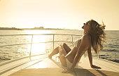 Beautiful blonde woman wearing a white bikini sitting on the deck of a yacht sunbathing on a summer day