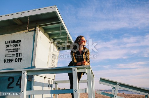 Young woman enjoying the beautiful ocean view from the Venice beach in Los Angeles, California. She is wearing casual clothing, an olive colored jacket, having a relaxed afternoon.