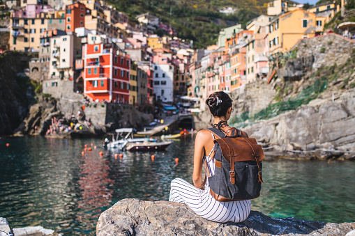 Female tourist relaxing by the sea. She is looking at the beautiful town Riomaggiore, Cinque Terre