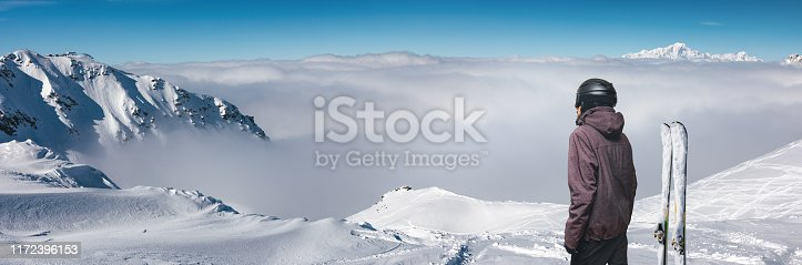 Skier enjoying the view on the top of the mountain. This image is a composite.