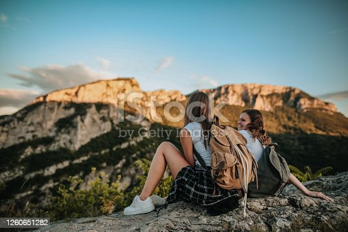 Two young female friends on top of a mountain