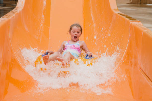 enjoying the waterslide - children play water park stock photos and pictures