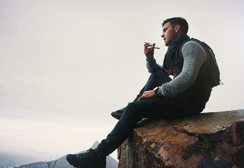 Shot of a young man talking on a cellphone while sitting on a mountain cliff