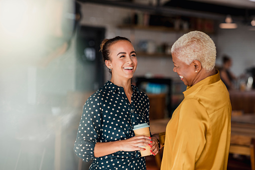 Two women colleagues laughing while standing in a cafe at their workplace. One of the women is holding a take out hot drink cup.