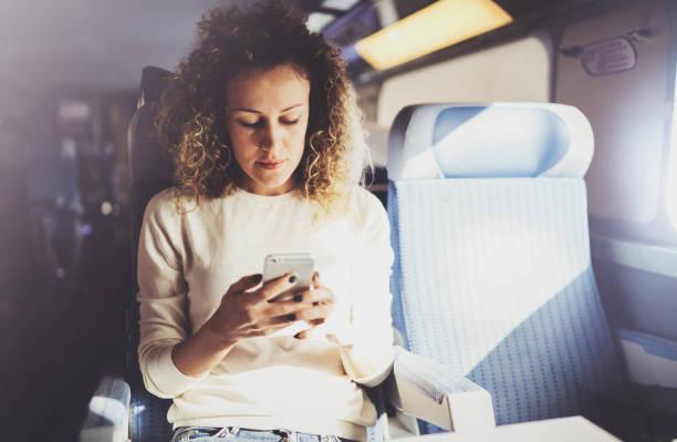 Genießen Reisekonzept. Junge hübsche Frau Touristen reisen mit dem Zug sitzen am Fenster mit Smartphone. – Foto
