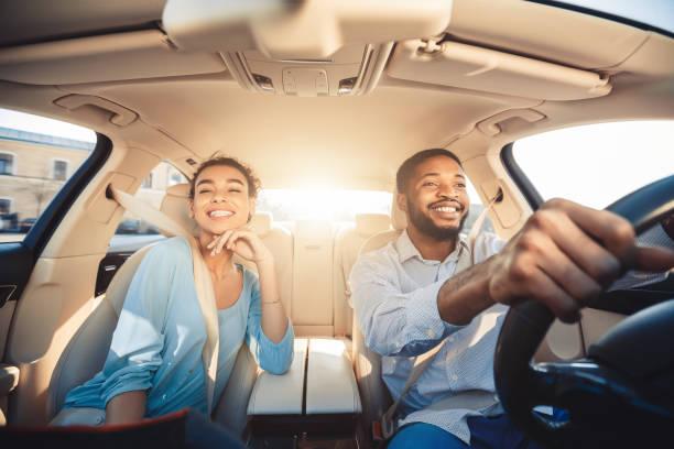 godendosi il viaggio. coppia africana eccitata alla guida di un'auto - auto foto e immagini stock
