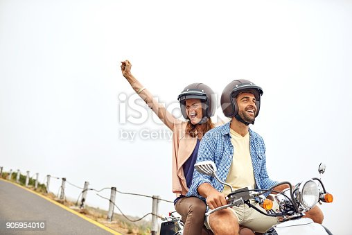 Shot of an adventurous couple out for a ride on a motorbike