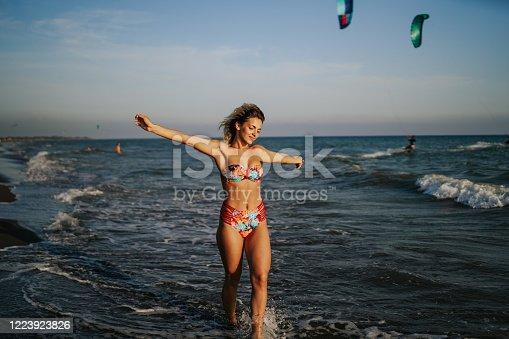 Beautiful woman in bikini enjoying sunny summer walk on the beach