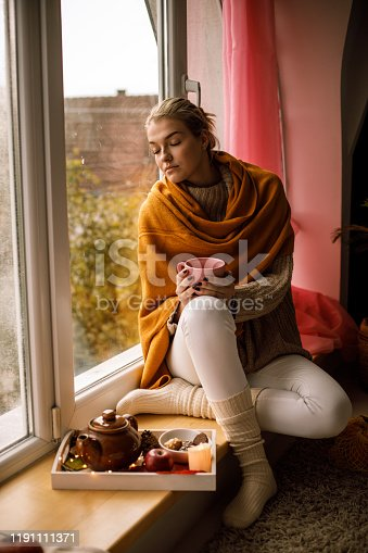 909062786 istock photo Enjoying warm cup of tea on a window cell 1191111371