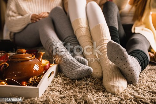 Lower section of three unrecognizable young girlfriends sitting on the bedroom floor in their cozy socks and hanging out together while enjoying some warm tea on a cold autumn day.