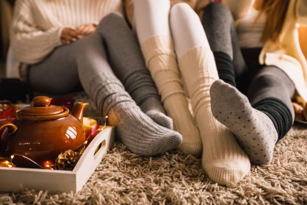 genießen sie warmen tee in gemütlicher socke an einem kalten herbsttag - behaglich stock-fotos und bilder
