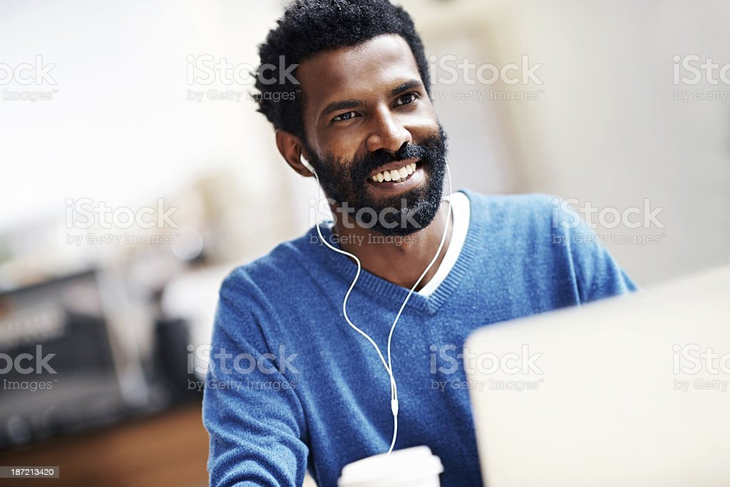 Enjoying work and play together A man sitting in a coffee shop working on his laptop and smiling 20-29 Years Stock Photo