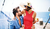 Young couple drinking white wine and enjoying together at yacht party.