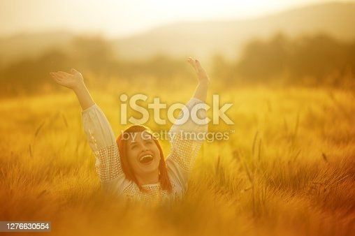Redhead woman with arms raised enjoying carefree time at the countryside in the meadow