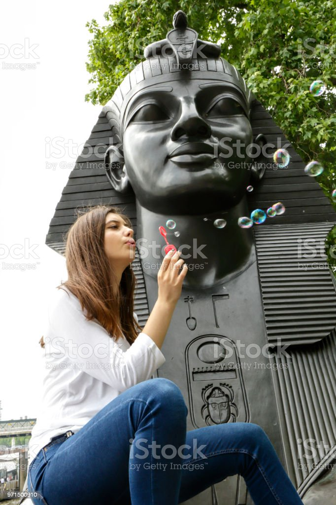 Enjoyment blowing bubbles by a London Sphinx Bulgarian outdoor girl stock photo