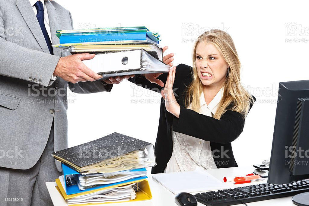 Enough already! Overworked young businesswoman rebels against extra workload royalty-free stock photo
