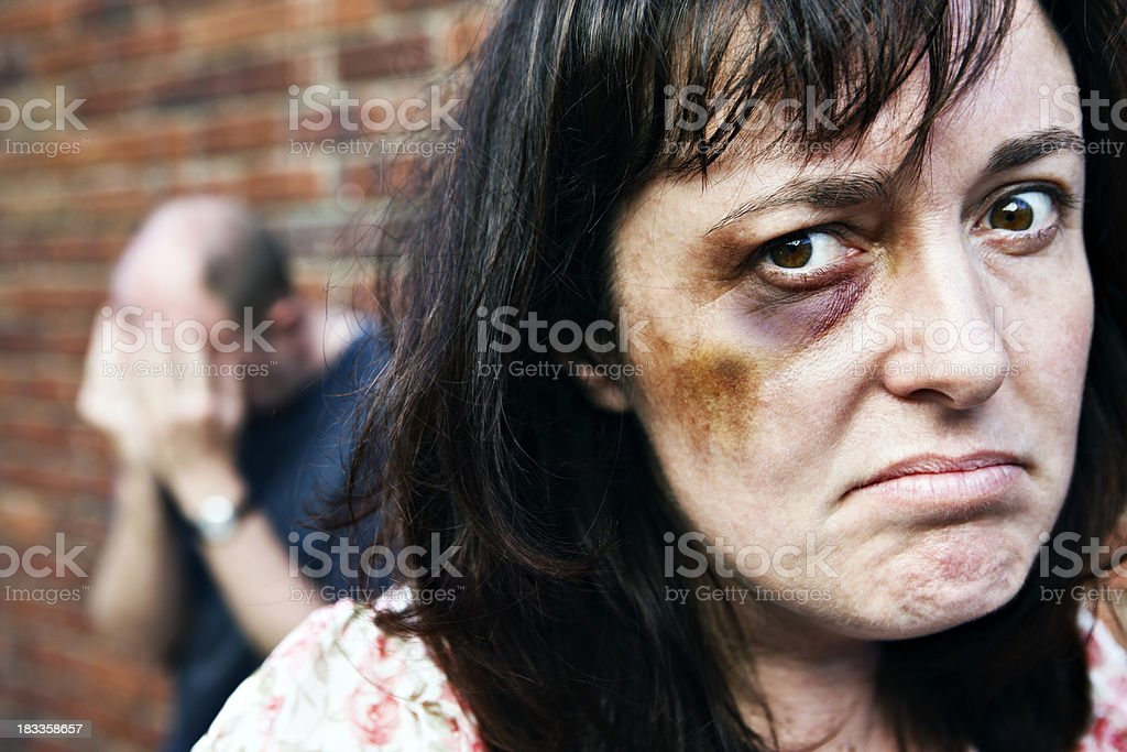 Enough! Angry battered woman glares; man has head in hands stock photo