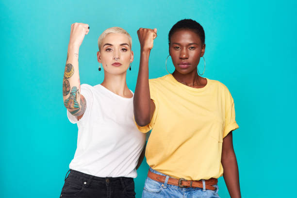 Enough is enough! Studio shot of two young women raising their fists in solidarity against a turquoise background women's rights stock pictures, royalty-free photos & images