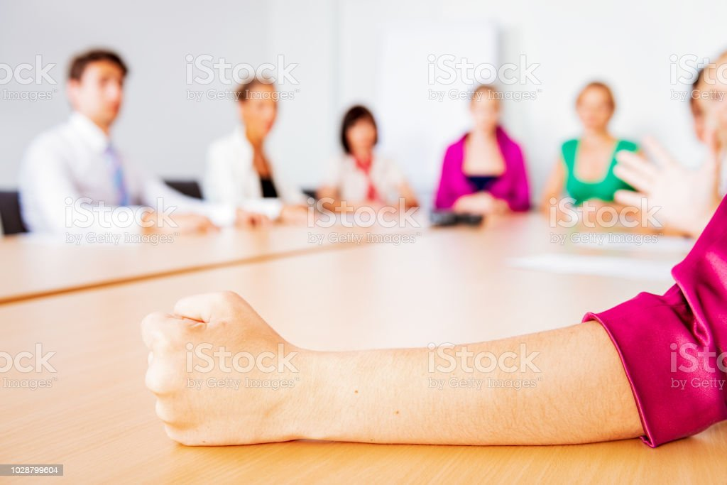 Frustrated manager - a woman\'s fist on the board room table during a...