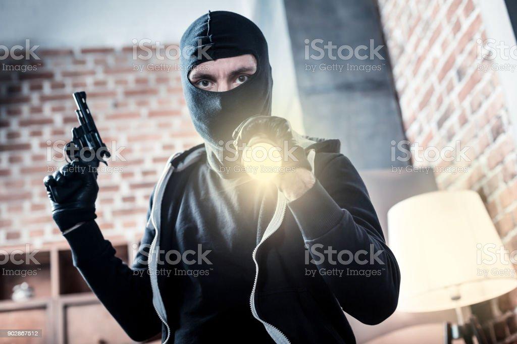 Criminoso enfurecido segurando uma arma e uma tocha - foto de acervo