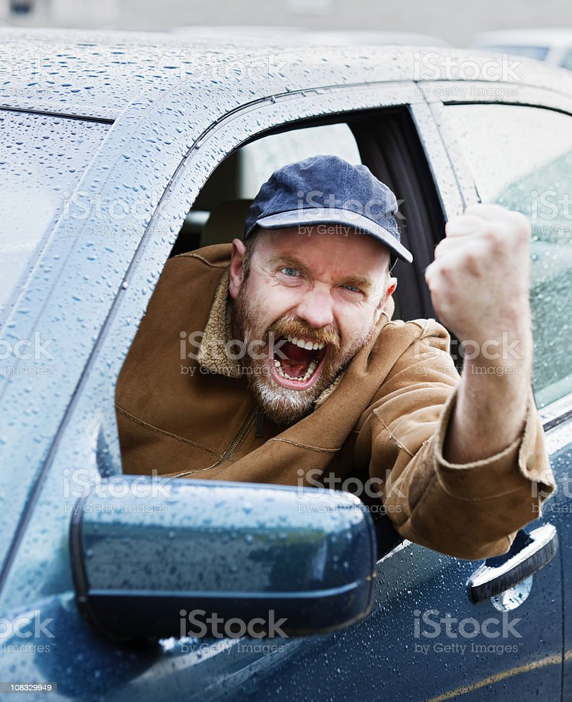 Enraged driver shakes fist out of car window royalty-free stock photo