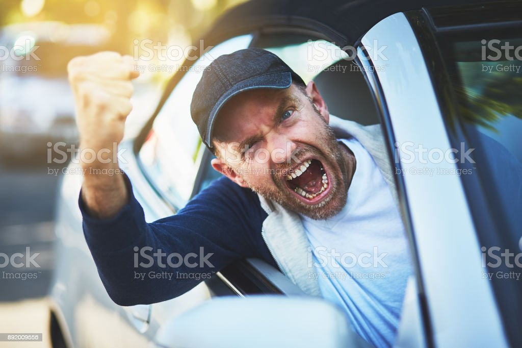Enraged male driver shakes fist, shouting through car window stock photo