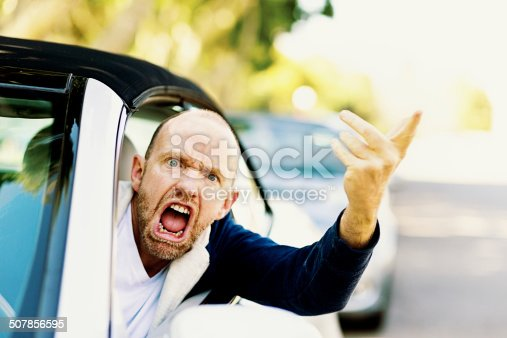 A furiously angry male driver grimaces, gesturing threateningly through the car window in a bout of road rage!